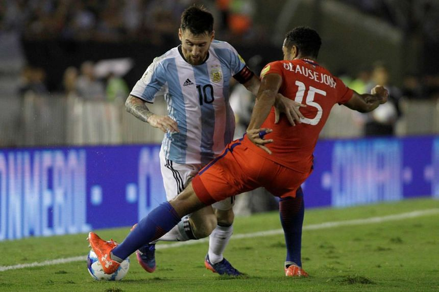 Argentina's Lionel Messi (left) and Chile's Jean Beausejour competing for the ball.