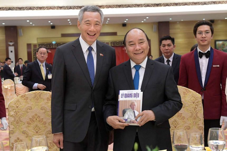Singapore's Prime Minister Lee Hsien Loong presenting Mr Lee Kuan Yew's memoirs to Vietnam's Prime Minister Nguyen Xuan Phuc during an official dinner at the Banquet Hall in the International Conference Centre in Hanoi on March 23, 2017.