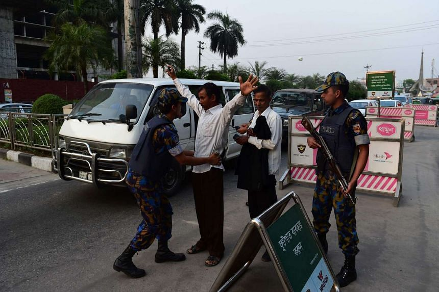 Bangladesh security personnel frisk a traveller at a checkpoint at the entrance to Hazrat Shah Jalal International Airport in Dhaka on March 17, 2017, following a suicide bomb explosion at a military camp in the city.