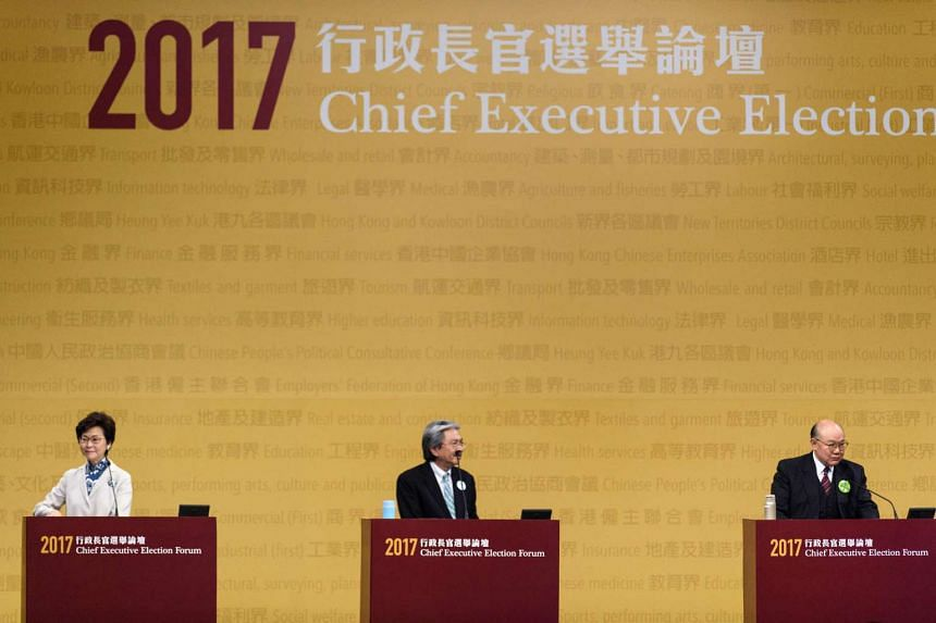 """Hong Kong's chief executive candidates (from left) Carrie Lam, John Tsang and Woo Kwok-hing look on as the Chief Executive Election Forum was interrupted by pro-democracy lawmaker """"Long Hair"""" Leung Kwok-hung in Hong Kong on March 19, 2017."""