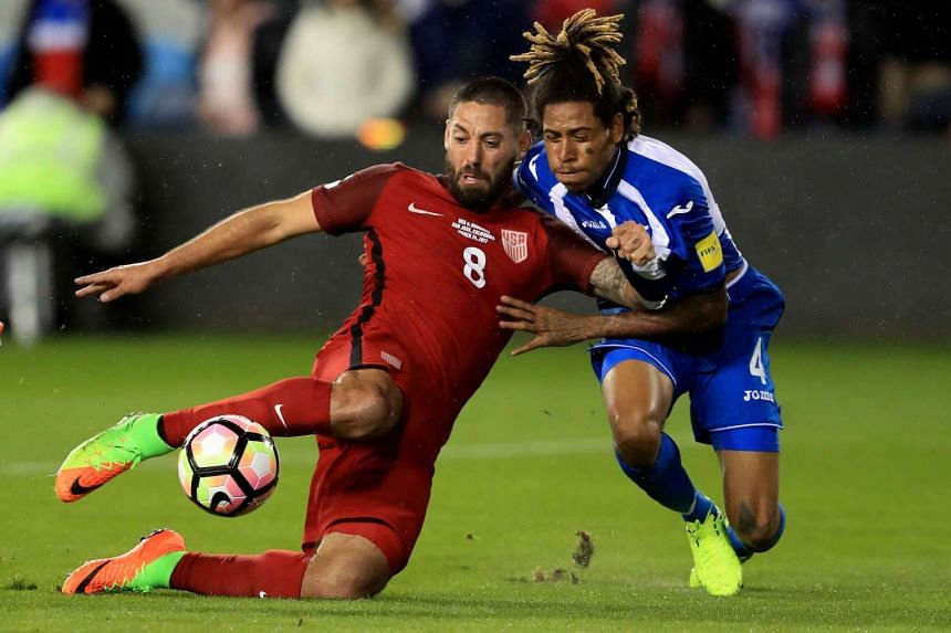 Clint Dempsey (Left) of the United States scores a goal as Henry Figueroa (Right) of Honduras defends during their FIFA 2018 World Cup Qualifier at Avaya Stadium on March 24, 2017.