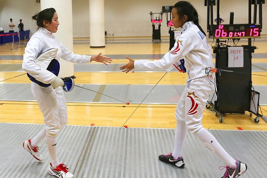 Singapore national junior fencer Kiria Tikanah Abdul Rahman (right) shaking the hand of her Singapore Sports School's opponent Michelle Lee. Kiria beat Lee 15-6 to win the Schools National A Division girls' individual epee event and will be confident