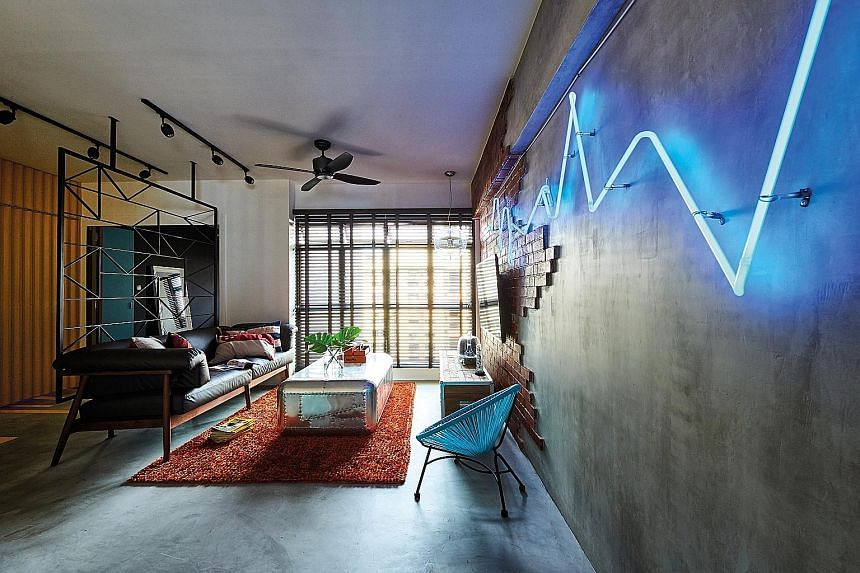 The customised neon light fixture in the living room, set against a faux brick and concrete screed feature wall, is inspired by stock graphs.