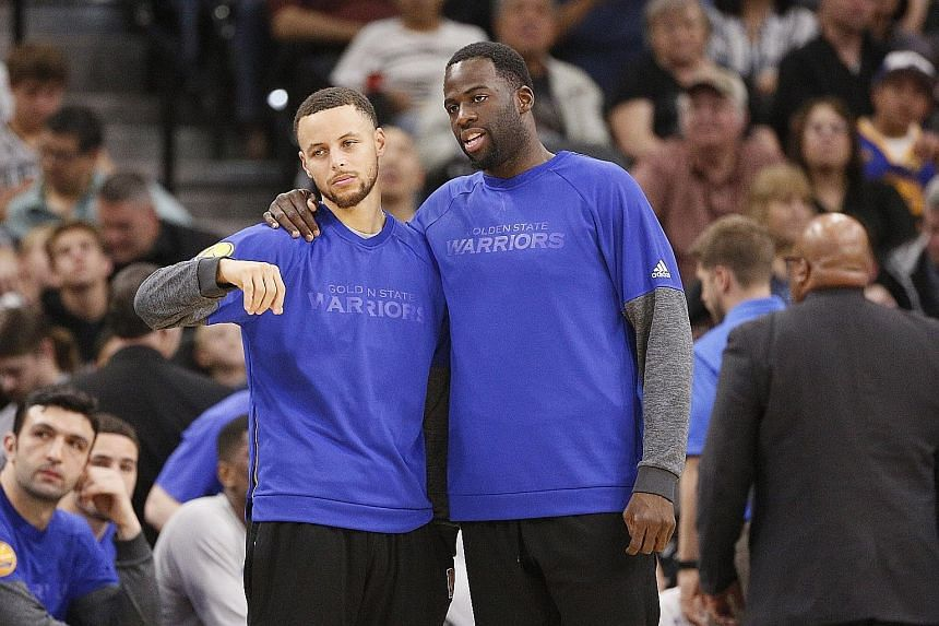 Stephen Curry (far left) and Draymond Green at the sidelines during Golden State's road loss to San Antonio earlier this month. Many coaches are juggling their line-ups to keep the big names fresh for the play-offs.