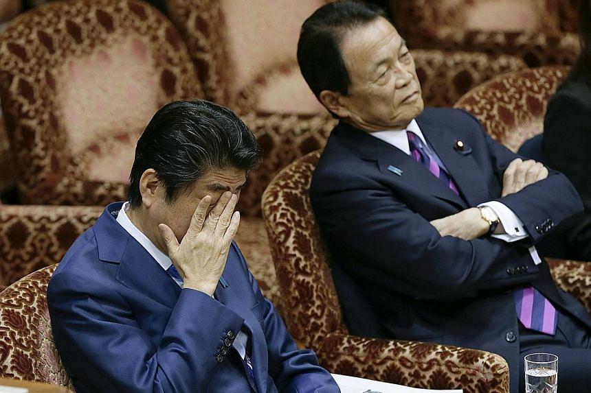 Mr Abe (left) and Finance Minister Taro Aso at an Upper House budget committee meeting in Parliament yesterday in Tokyo. Mr Aso said the land sale was completed with the proper procedures and pricing.