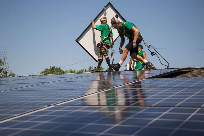 SolarCity employees installing solar panels on the roof of a home in Kendall Park, New Jersey, US, on July 28, 2015.
