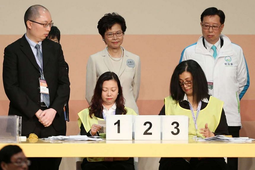 Hong Kong Chief Executive-elect Carrie Lam (standing, centre) looks on as officials count ballots at the Convention Center in Hong Kong on March 26, 2017.