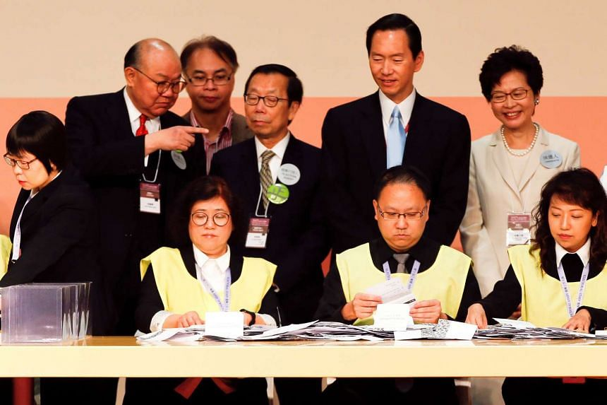 Candidates Woo Kwok Hing (left) and Carrie Lam (right) look as officials count votes during the election for Hong Kong's next Chief Executive.