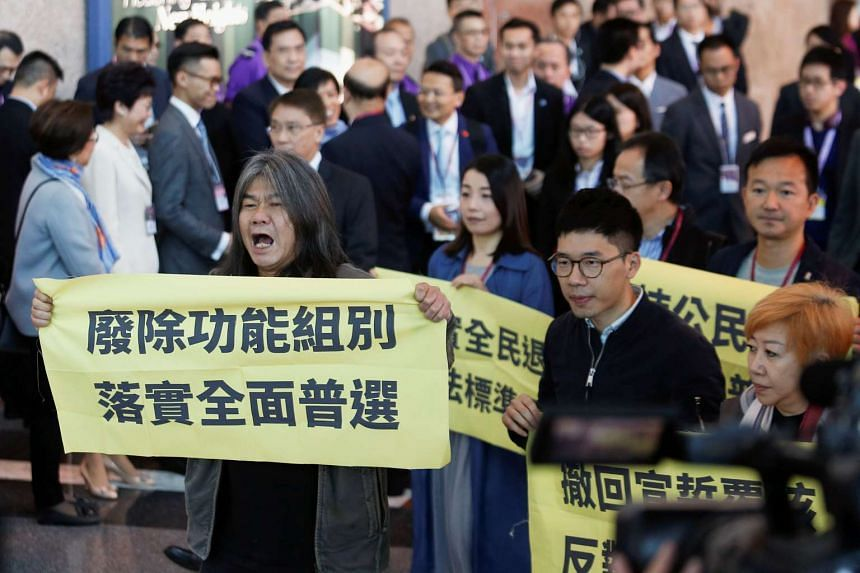 Pro-democracy activist Leung Kwok Hung (left) and other lawmakers chanting slogans and carrying banners demanding universal suffrage as they arrive for voting during the election for Hong Kong's next Chief Executive on March 26, 2017.