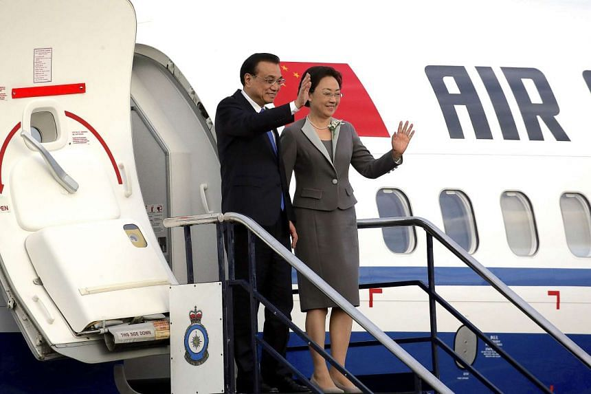 Chinese Premier Li Keqiang and his wife Cheng Hong wave as they arrive in Wellington on March 26, 2017.