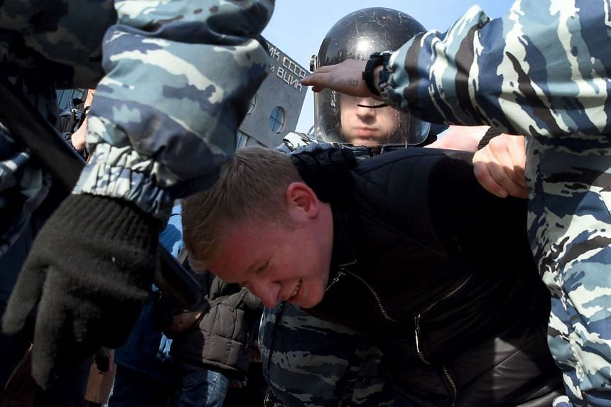Police officers detain a man during an unauthorised anti-corruption rally in central Moscow on March 26, 2017.