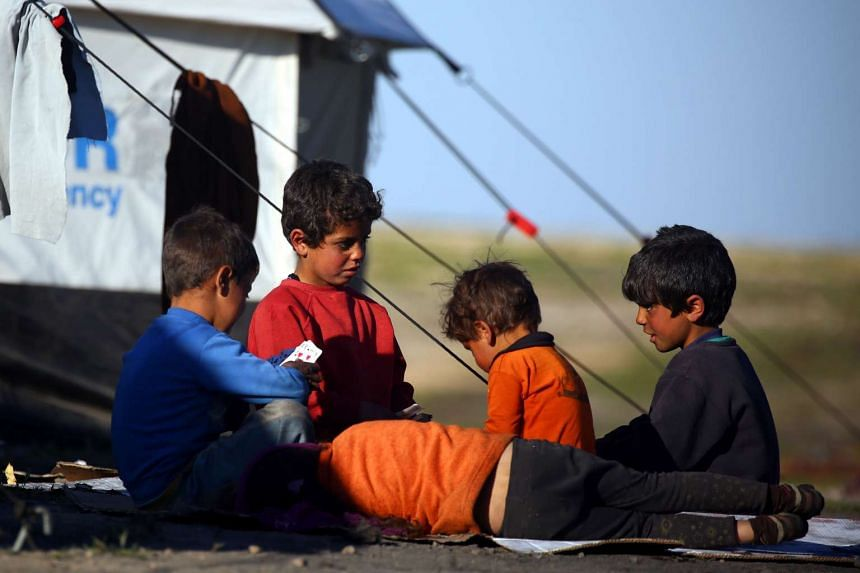 Syrian children play cards at a temporary refugee camp in the village of Ain Issa, housing people who fled the Islamic State group's Syrian stronghold Raqa.