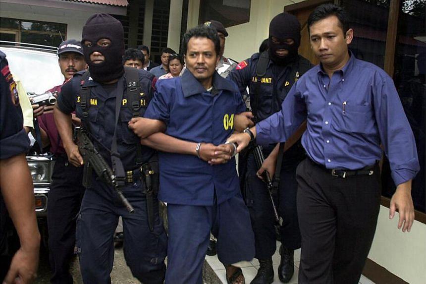 Mas Selamat Kastari (centre) leaving the Tanjung Pinang police station under heavy guard in 2003.