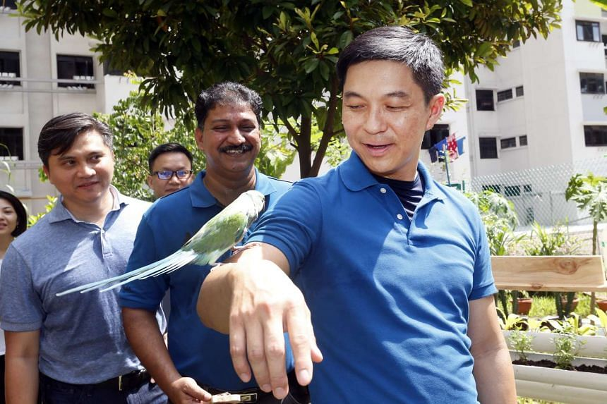 Minister Tan Chuan-Jin with a parrot during a visit to meet residents who are members of the Parrots Interest Group.