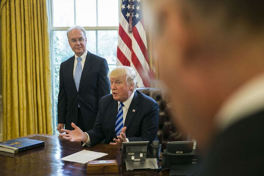 US President Donald Trump speaks about the House pulling its planned legislation to repeal the Affordable Care Act, as Health and Human Services Secretary Tom Price looks on, in the Oval Office.