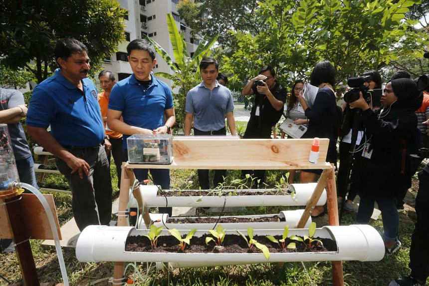 Minister Tan Chuan-Jin (second from left) activating the Micro-Bit Automated water system for the community garden by using a Bluetooth wireless communication device to activate the Micro:Bit Automated Water.