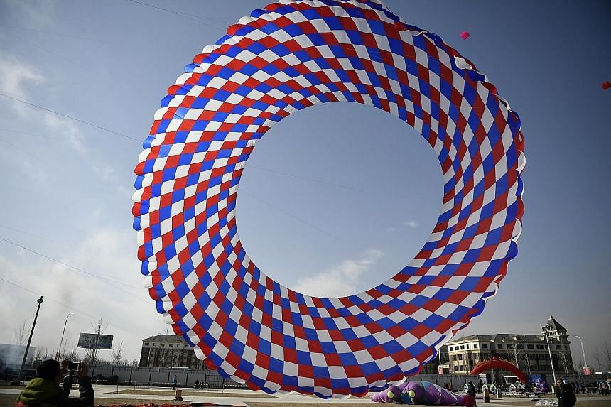 "A huge kite known as the ""ground-rolling dragon"" is a head-turner in Yinchuan, a city in north-central China's Ningxia province. As many as 1,000 kites took to the sky at the opening of the third Kite Culture and Arts Festival in Sanshayuan Internati"