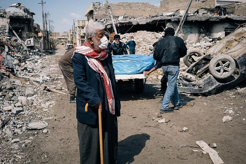 An elderly Iraqi reflects as bodies of civilians are carried out from the rubble of a bombed building in Mosul. Iraqi officials and witnesses say strikes in west Mosul have killed dozens of people in recent days, but the number of victims could not b