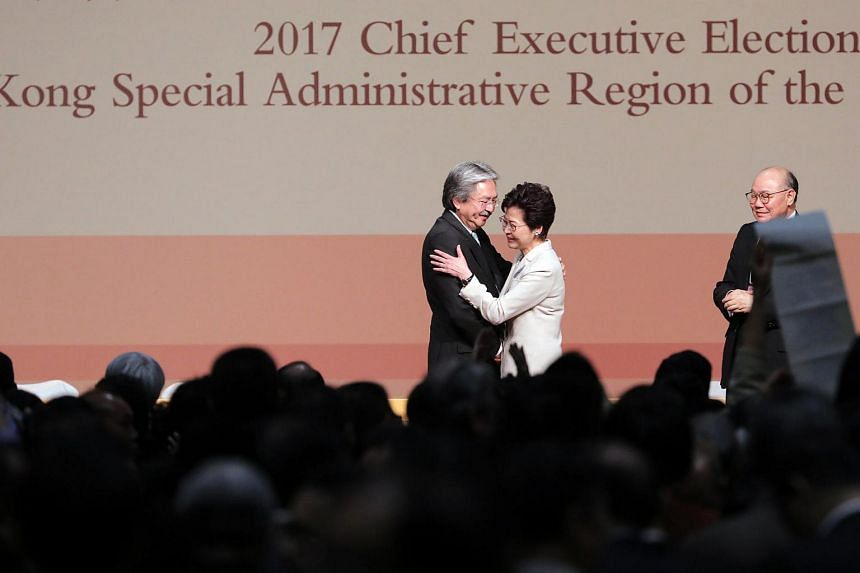 Candidates for Hong Kong's chief executive Carrie Lam, Hong Kong's former chief secretary (centre) hugs John Tsang, Hong Kong's former financial secretary, as Woo Kwok Hing, retired judge, looks on during the results announcement of the chief executi
