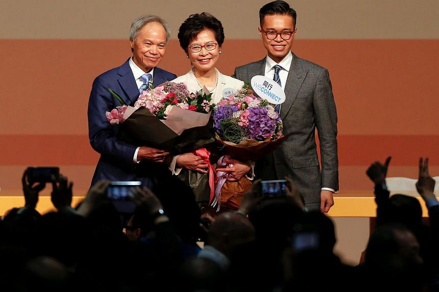 Carrie Lam is congratulated by her husband and son after she won the election for Hong Kong's next Chief Executive in Hong Kong.