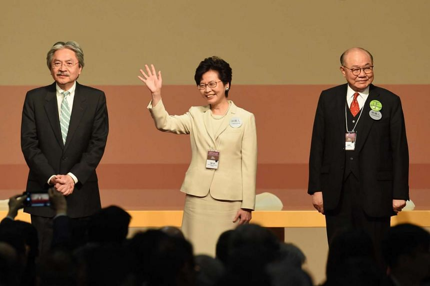 Hong Kong's new-elected Chief Executive Carrie Lam waves, while her defeated opponents Woo Kwok Hing (right) and John Tsang (left) look on, after winning the poll on March 26, 2017.
