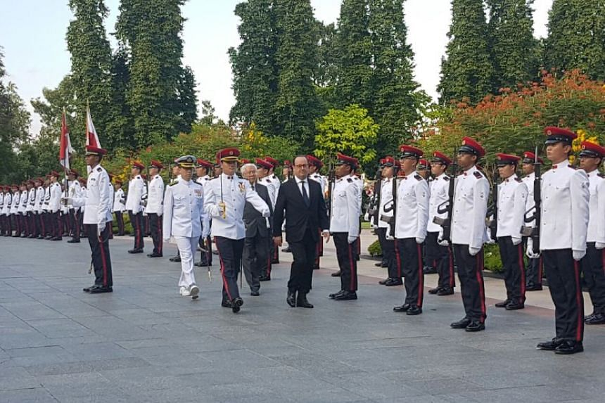 President Tony Tan and his French counterpart Francois Hollande inspect the guard before a state dinner on March 26, 2017.