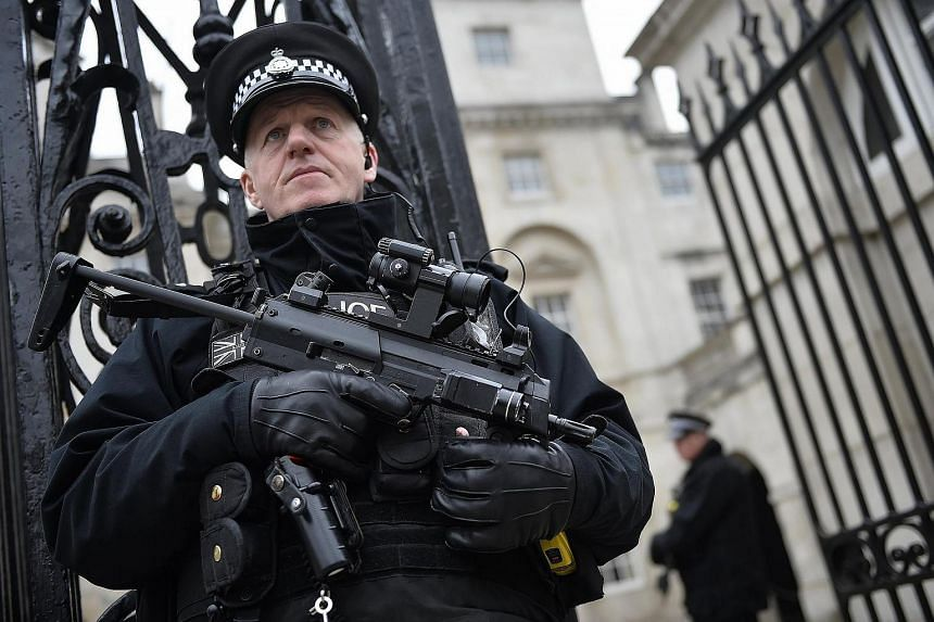 An armed policeman stand guards in Westminster, near the scene of the attack on March 22, 2017 in central London.