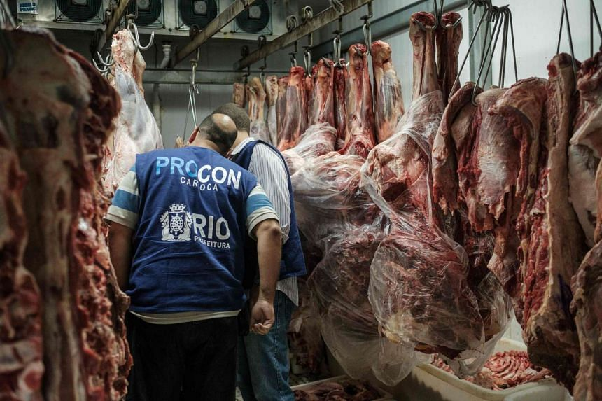 Staff from Rio de Janeiro state's consumer protection agency, PROCON, inspect meat in at a supermarket in Rio on March 24, 2017.