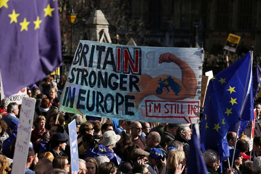 Demonstrators hold a placard during an anti Brexit, pro-European Union (EU) march in London on March 25, 2017.