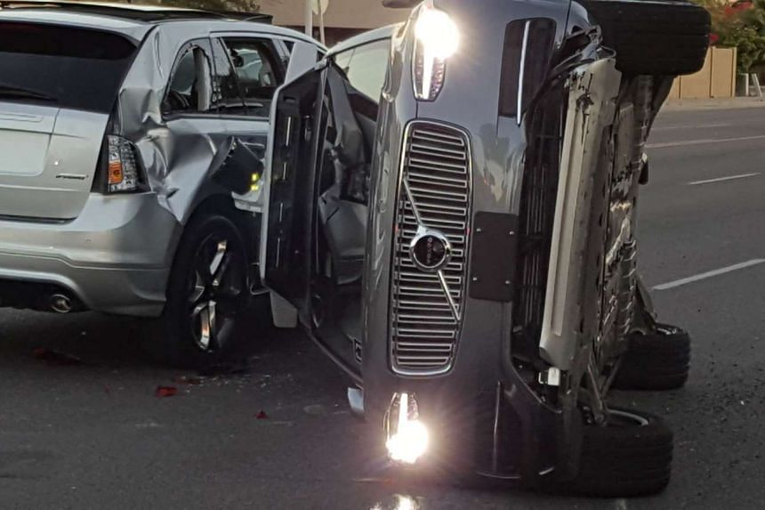 A self-driven Volvo SUV owned and operated by Uber Technologies is flipped on its side after a collision in Tempe, Arizona on March 24, 2017.