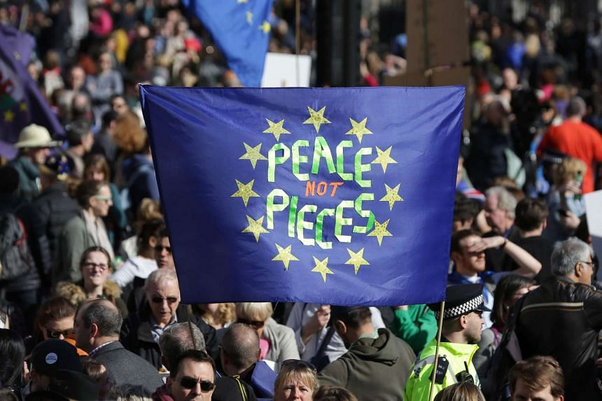 Demonstrators hold a banner written on an EU flag in Parliament Square during an anti-Brexit march, ahead of the government's planned triggering of Article 50 next week.