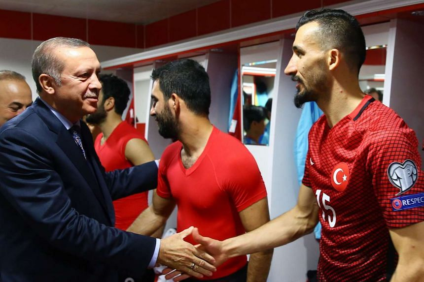 Turkey's President Recep Tayyip Erdogan (left) shakes hands with Turkey`s defender Mehmet Topal during the World Cup qualificater between Turkey and Finland  on March 24, 2017.