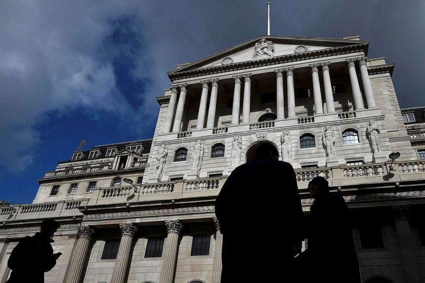 City workers walk past the Bank of England in the City of London.