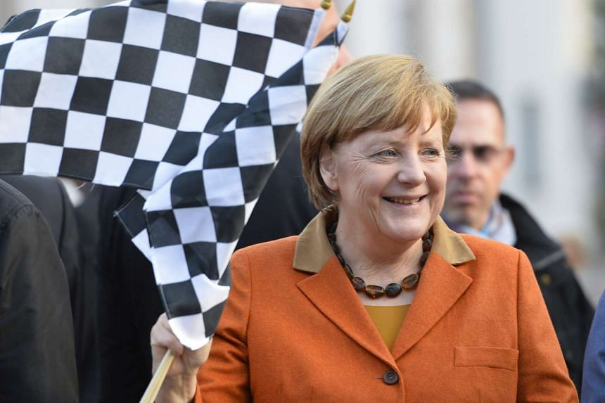 Merkel waves a starter flag symbolising the last 72 hours of the election campaign in Saarland, March 23, 2017.