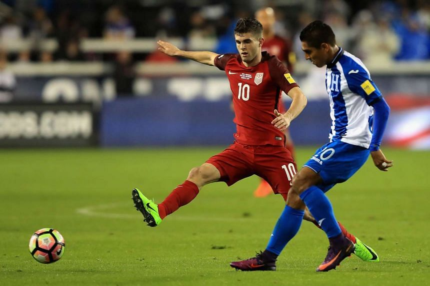 Christian Pulisic (left) of the United States defends against Jorge Claros of Honduras during their 2018 World Cup Qualifier on March 24, 2017.