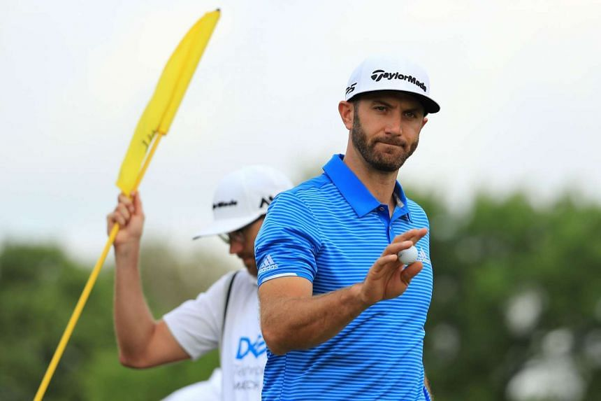 Dustin Johnson waves after putting for birdie on the 1st hole of his match during the semi-finals.