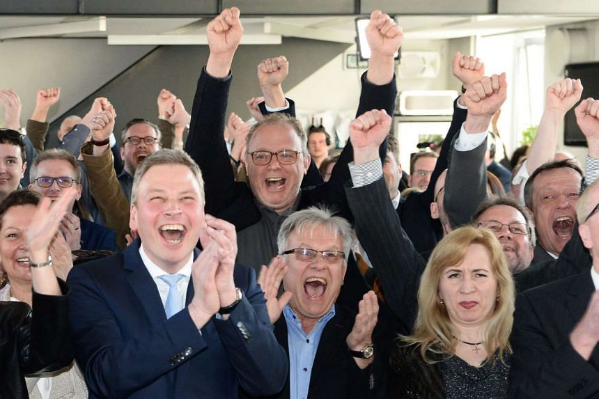 Supporters of the Christian Democratic Union (CDU) react after exit poll results of the state election in Saarland are announced.