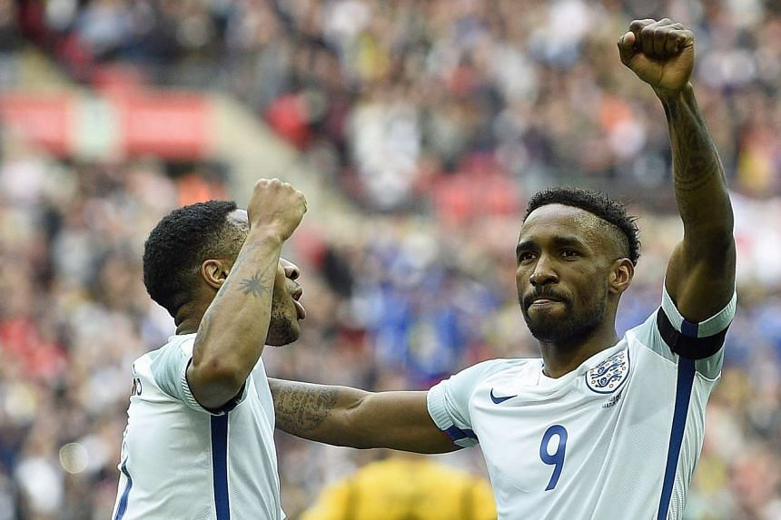 England's Jermain Defoe celebrates scoring their first goal against Lithuania with goal maker Raheem Sterling.