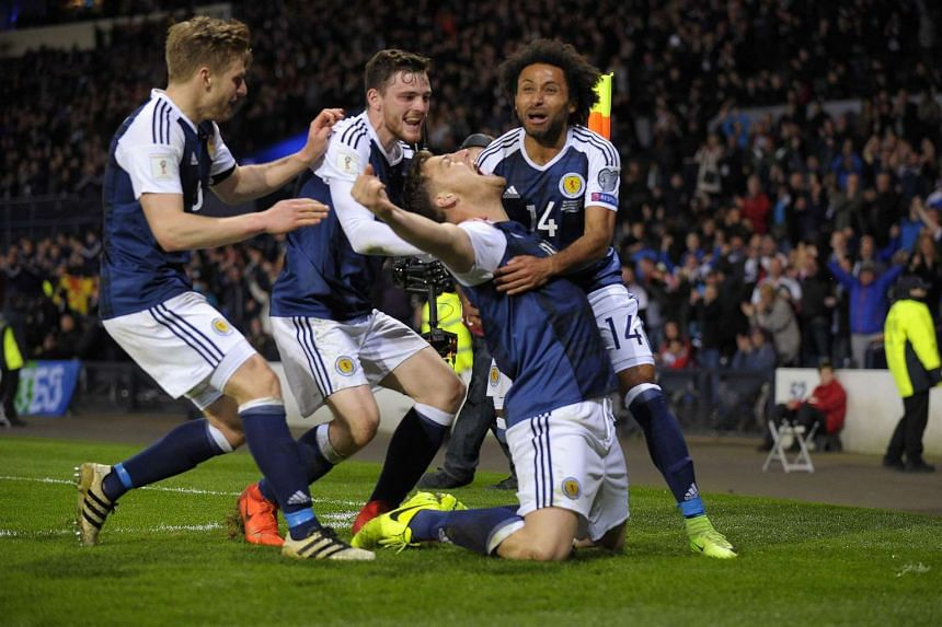 Scotland's striker Chris Martin (second from right) celebrates with team-mates after scoring the only goal of the World Cup 2018 qualification football match between Scotland and Slovenia on March 26, 2017.