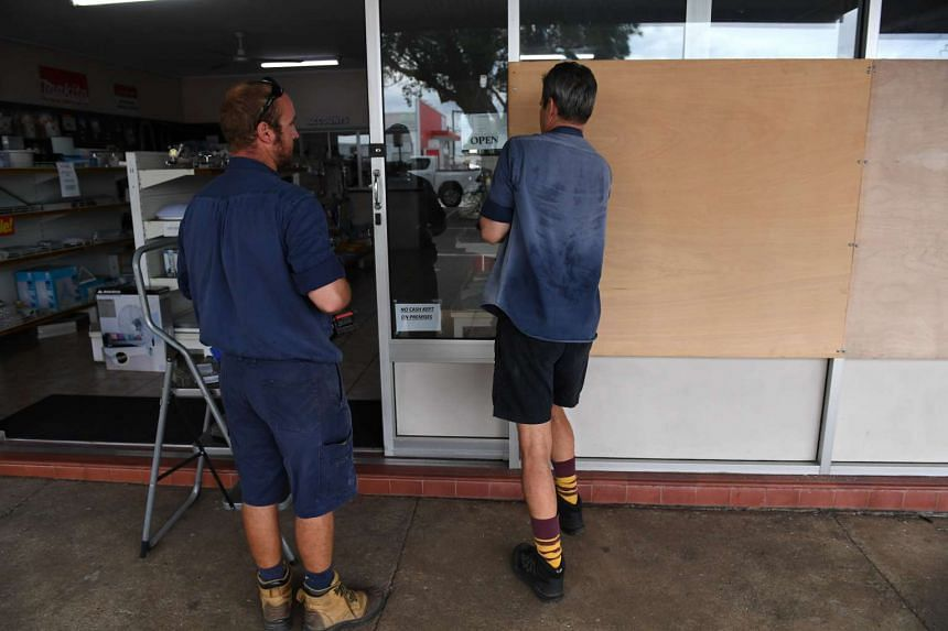 Locals board up a front window of a business in Ayr near Townsville, Queensland, Australia, on March 27, 2017.