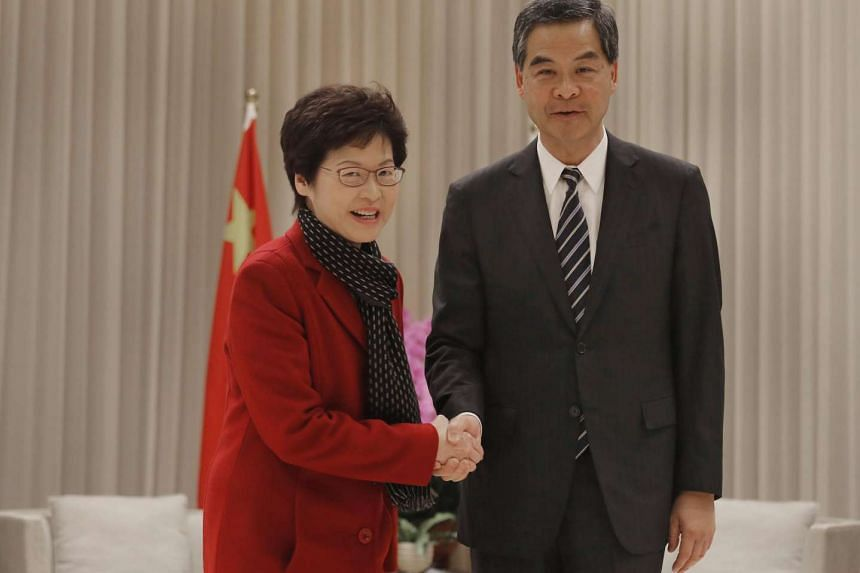 Hong Kong's chief executive-elect Carrie Lam (left) shakes hands with current chief executive Leung Chun-ying at government headquarters in Hong Kong