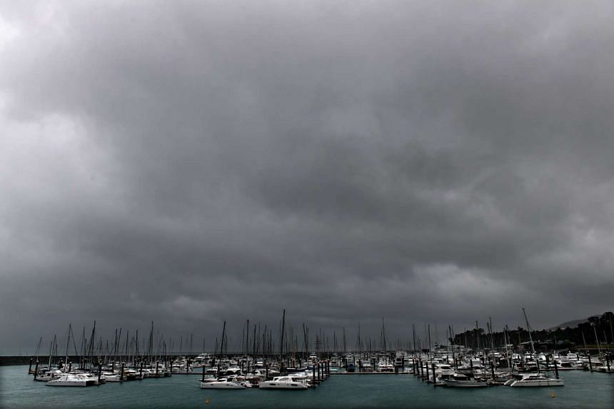 Dark clouds approach over boats at Airlie Beach, Queensland on March 27, 2017.