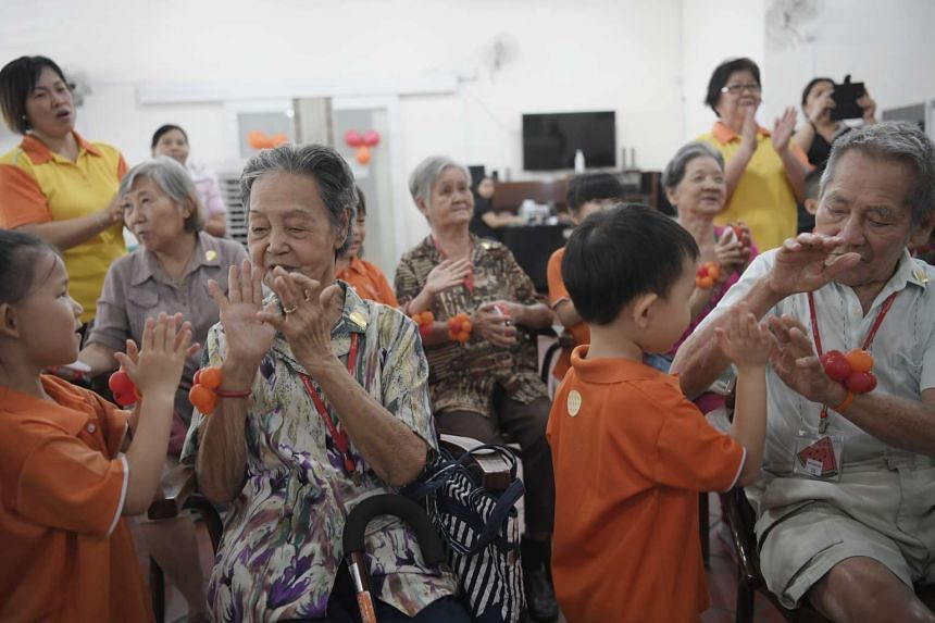Madam Tan Siam Eng, 88 (left) and Mr Gan Seng Cho (right), 90, singing and playing with kindergarten 2 pupils from My First Skool.