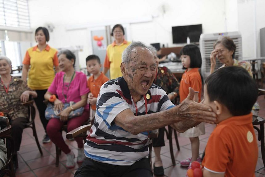 Mr Michael Tay, 94, laughs as he plays with a kindergarten 2 pupil from My First Skool at the launch of NTUC First Campus and NTUC Health's novel inter-generational programme.