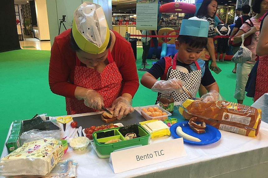 Families taking part in preparing nutritious food in a Healthy Lunchbox competition at United Square yesterday to launch the 10th anniversary of the Cold Storage Kids Run. This year's run will take place on May 28 at Sentosa's Palawan Green, and all