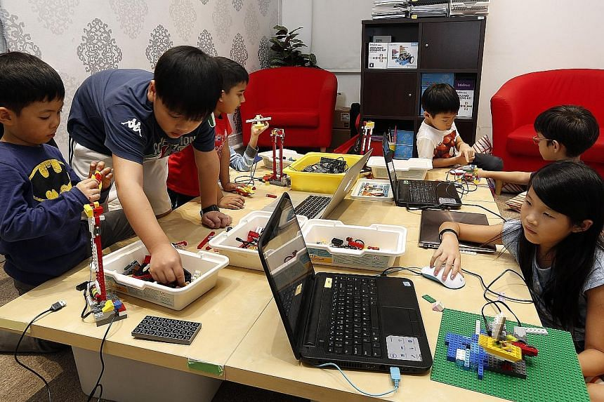 Children learning how to make their own robots using Lego pieces during a holiday workshop on robotics and game design at In3Labs. Robots and computer programs are helping do jobs ranging from delivering room service to providing financial advice, an