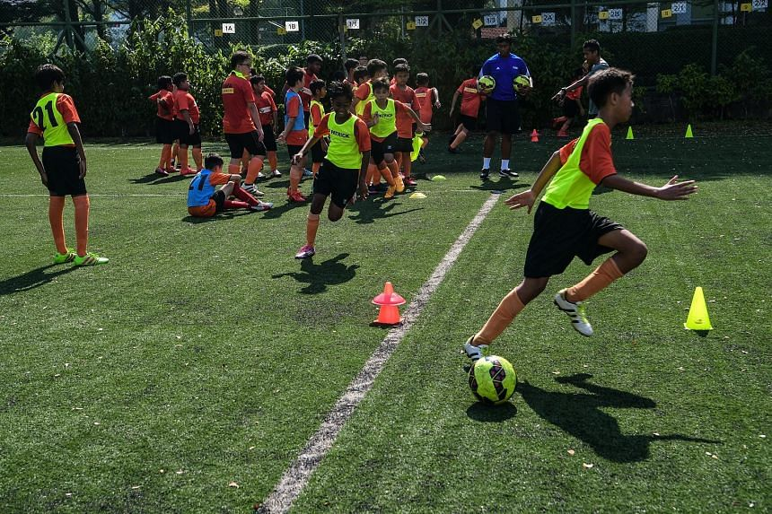 Children between the ages of five and 14 at a regular football training session conducted by the Yuhua Albirex Football Academy yesterday at Shuqun Secondary School. The organisation is run by Yuhua Community Sports Club, while S-League club Albirex