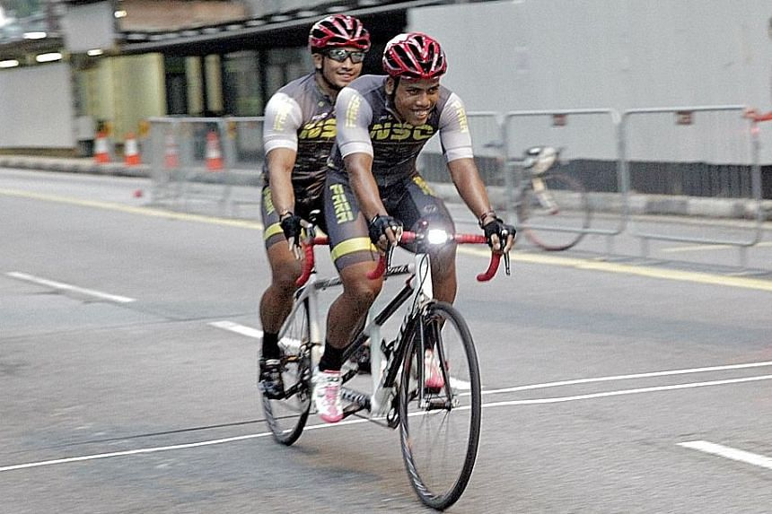 Visually-impaired Afiq Afify Rizan (rear seat) and his able-bodied partner Khairul Adha Rasol crossing the finish line yesterday to win the National Para Cycling Road Championship and International Invitational. The event, held on Cecil Street and Ro