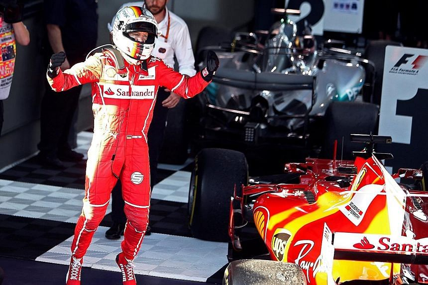 Ferrari's Sebastian Vettel celebrating after his win at Albert Park yesterday. Despite Mercedes' Lewis Hamilton starting on pole, he lost the lead to the German driver after a pit stop.