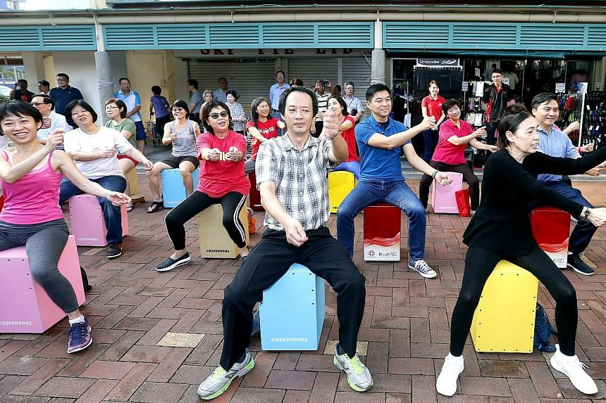Mr Tan and Mr Saktiandi (both in second row) joining residents in a performance yesterday during a ministerial community visit to Toa Payoh East-Novena ward.